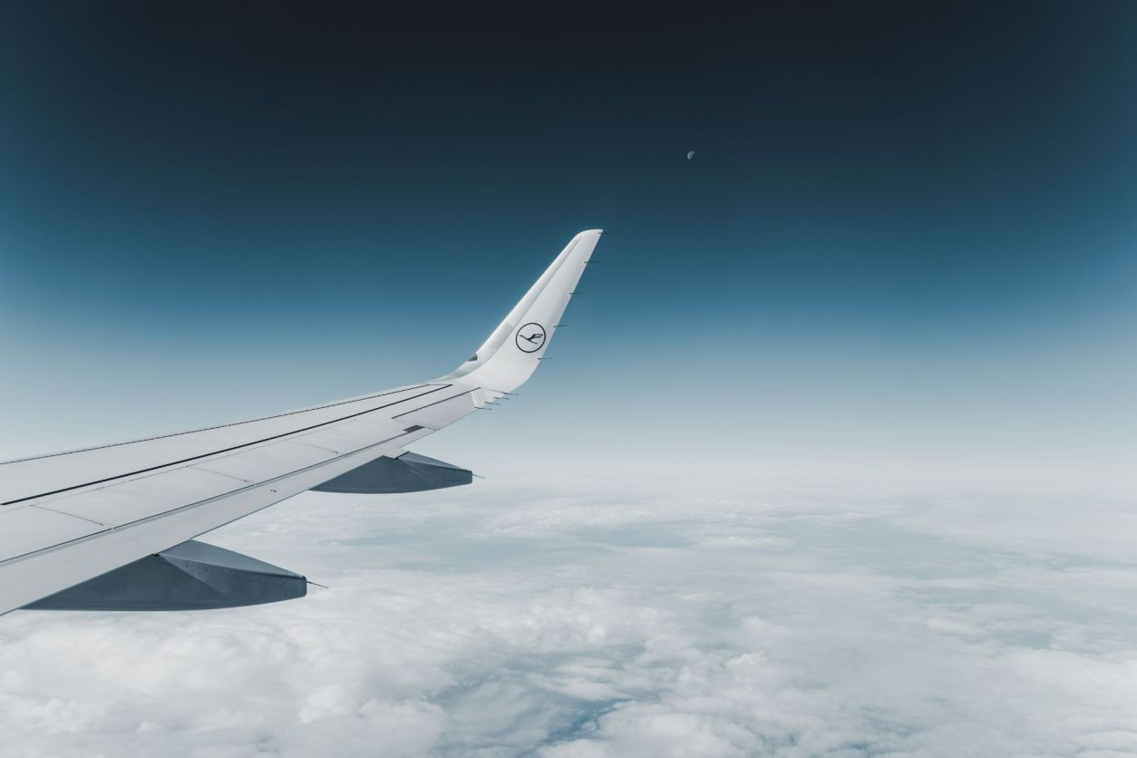 wing-of-airplane-flying-through-sky-at-night-above-the-clouds-sustainable-travel-tips
