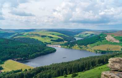 picturesque-view-of-a-reservoir-bridge-and-rolling-green-hills-at-bamford-edge-in-the-peak-district