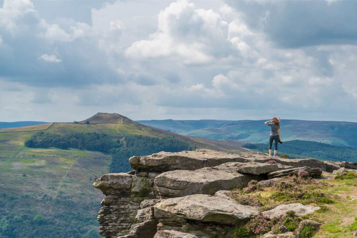 woman-standing-on-edge-of-cliff-looking-out-at-the-view-holding-a-camera-at-bamford-edge-in-the-peak-district