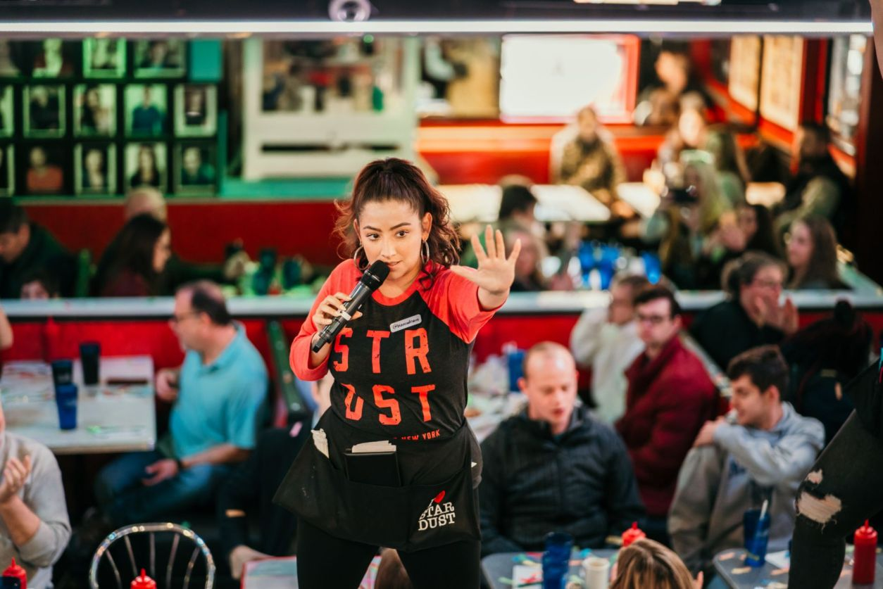 singer-at-ellens-stardust-diner-in-times-square-standing-on-table-dancing-and-singing-with-microphone-whilst-visitors-eat-in-the-background