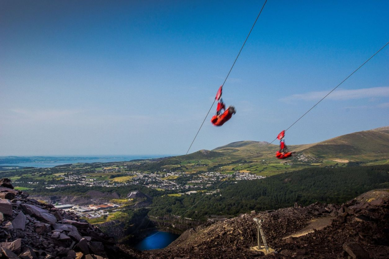 people-in-red-overalls-on-the-fastest-zip-line-in-the-world-going-over-a-quarry-in-the-mountains-north-wales-snowdonia-zip-world-adrenaline-junkie-bucket-list