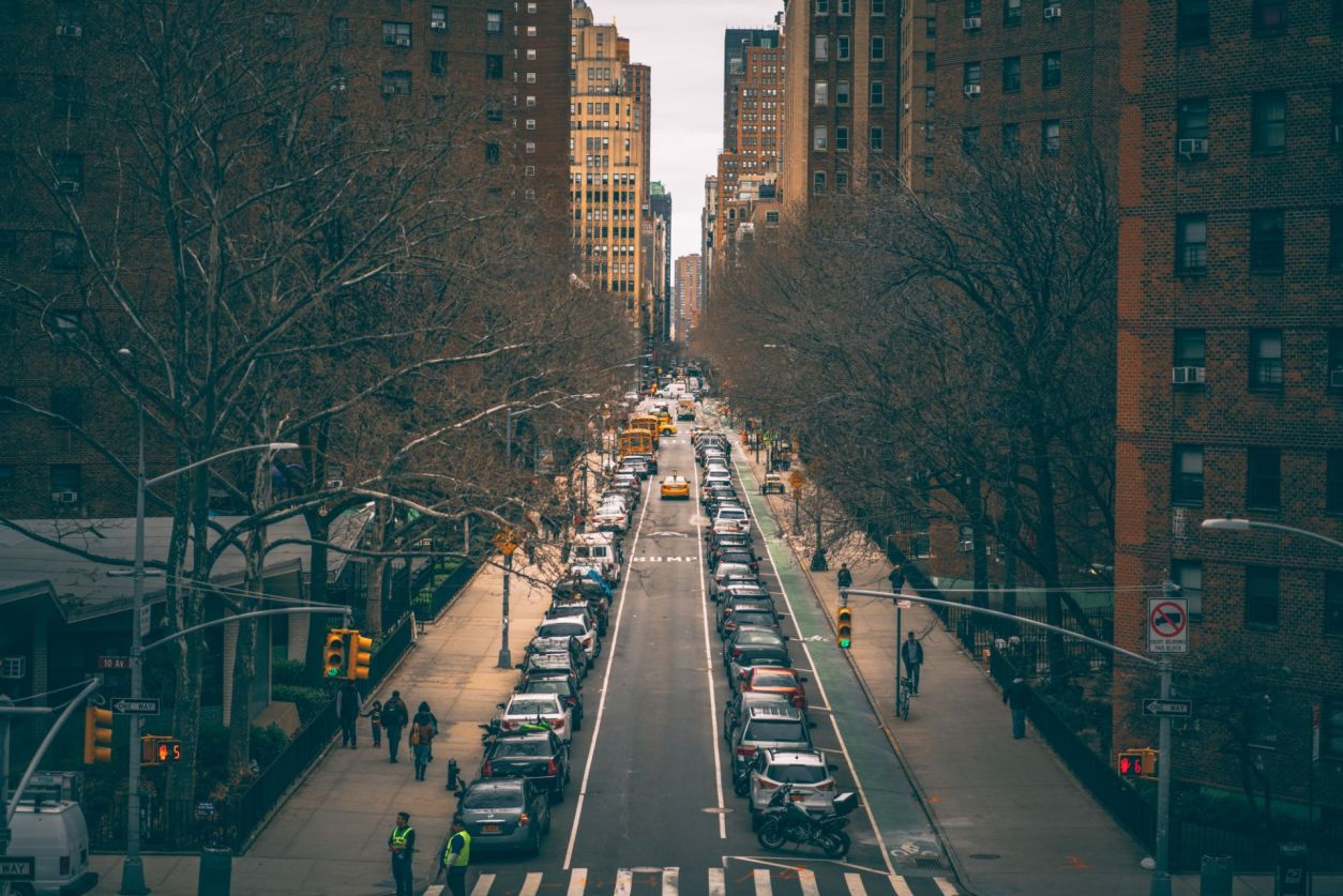 yellow-taxi-driving-down-a-tree-lined-street-in-manhattan-new-york