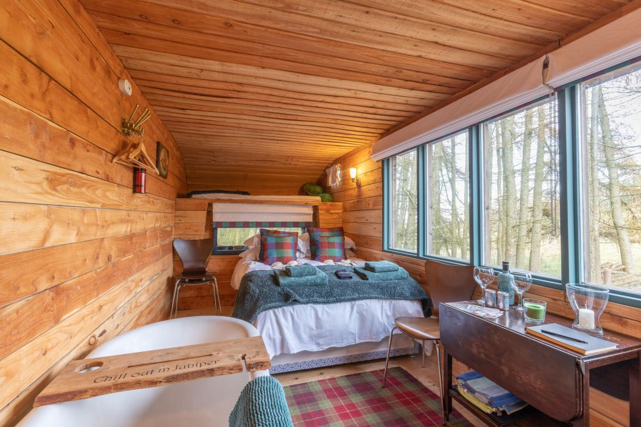 the-inside-of-a-hut-with-a-bed-bath-and-desk-juniper-horsebox-in-perth-and-kinross-glamping-with-hot-tub-in-scotland