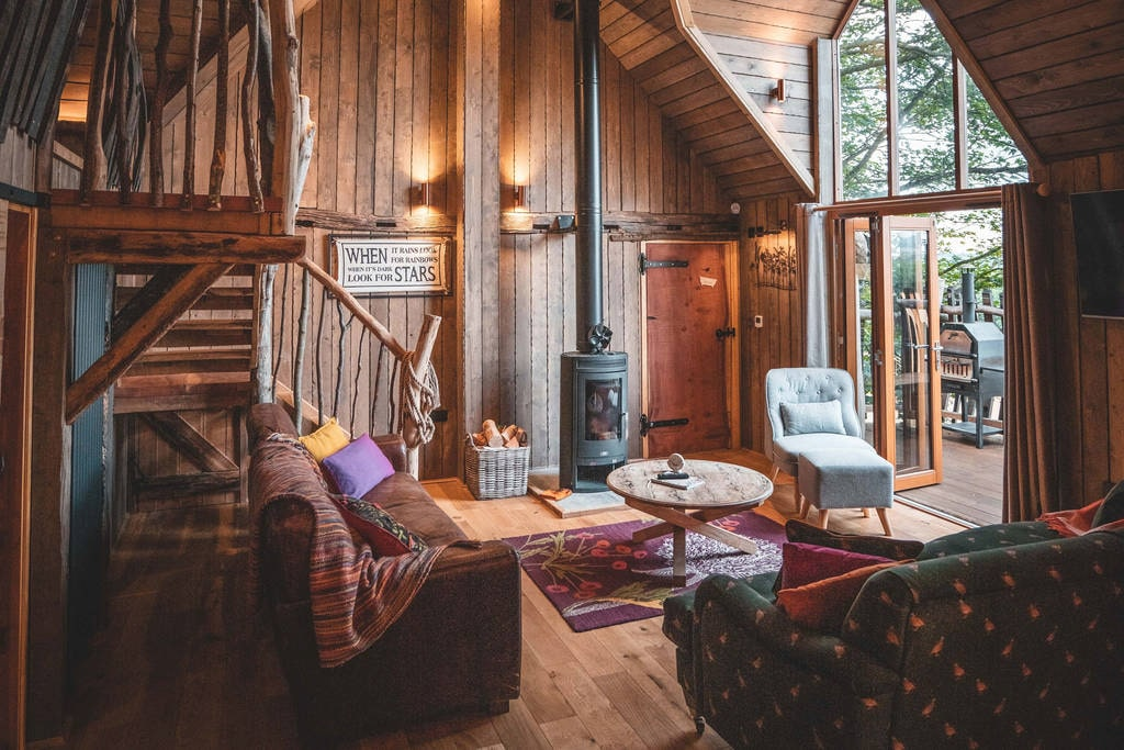 interior-of-rufus-roost-rustic-wooden-treehouse-living-room-with-sofas-chairs-and-log-burner-leading-out-to-a-porch-in-york