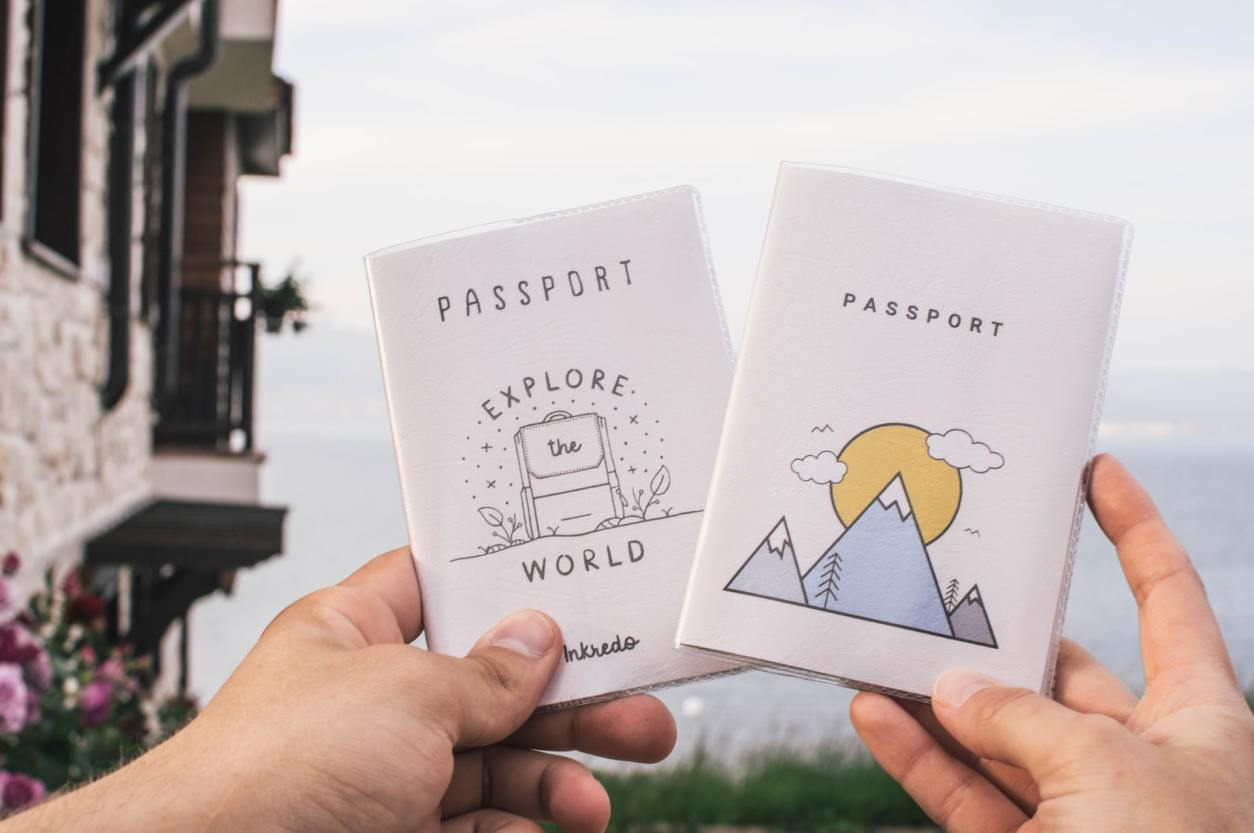 two-hands-holding-up-inkredo-passport-covers-explore-the-world-at-ski-resort-in-mountains