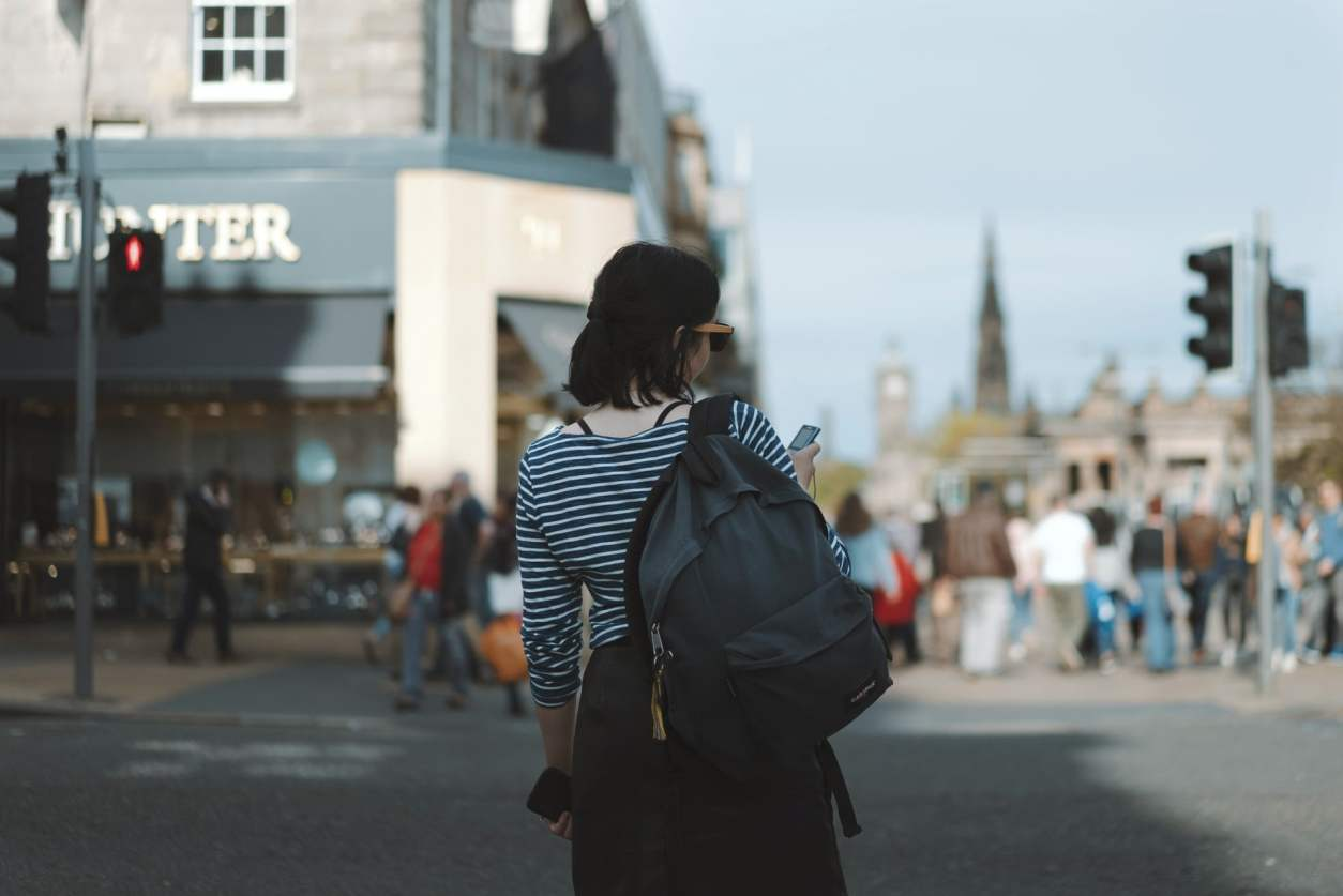 woman-with-backpack-and-ipod-about-to-cross-street-in-edinburgh-near-princes-street-gardens