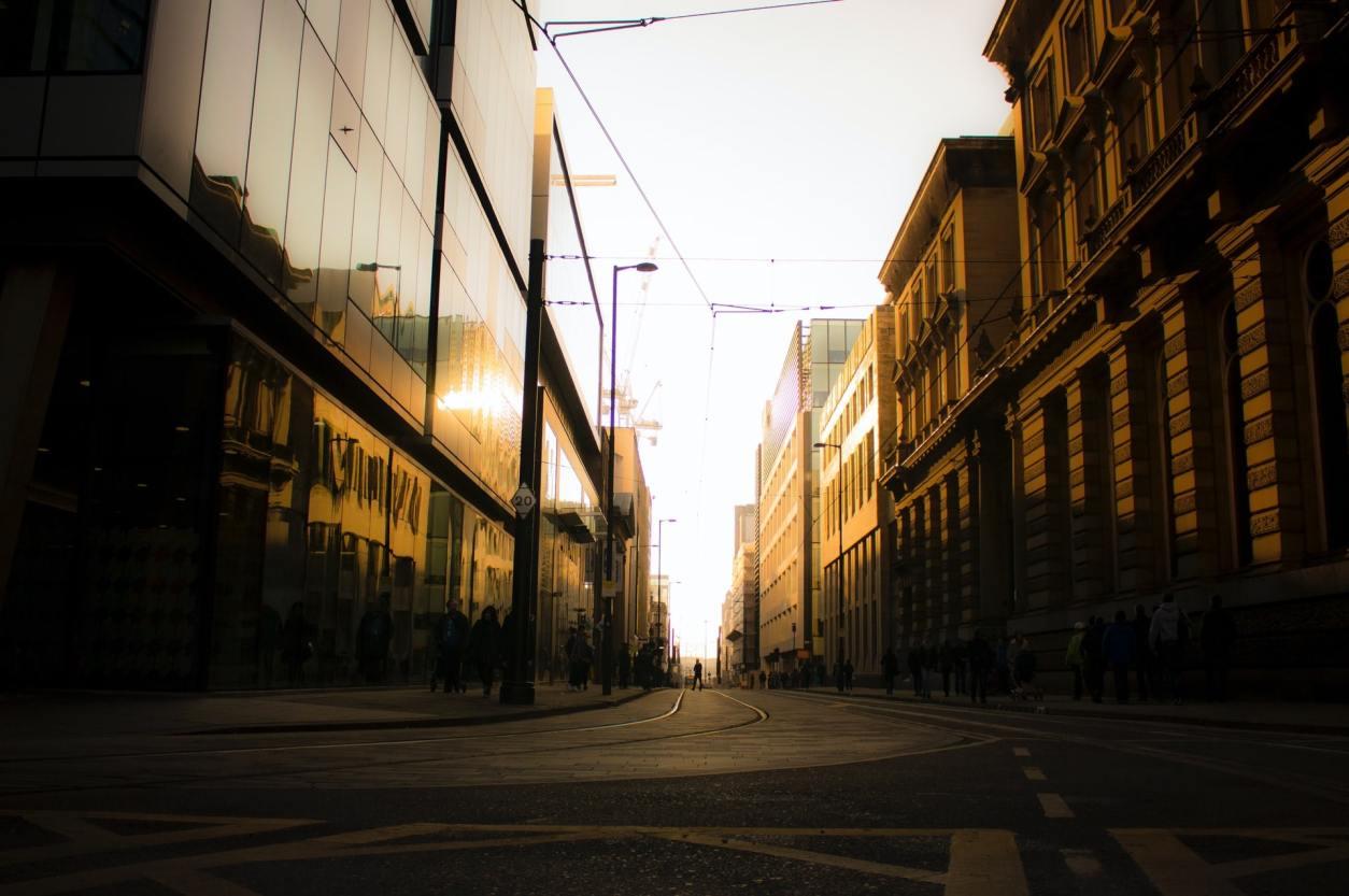golden-light-shining-through-city-street-on-tramlines-at-sunset-in-manchester