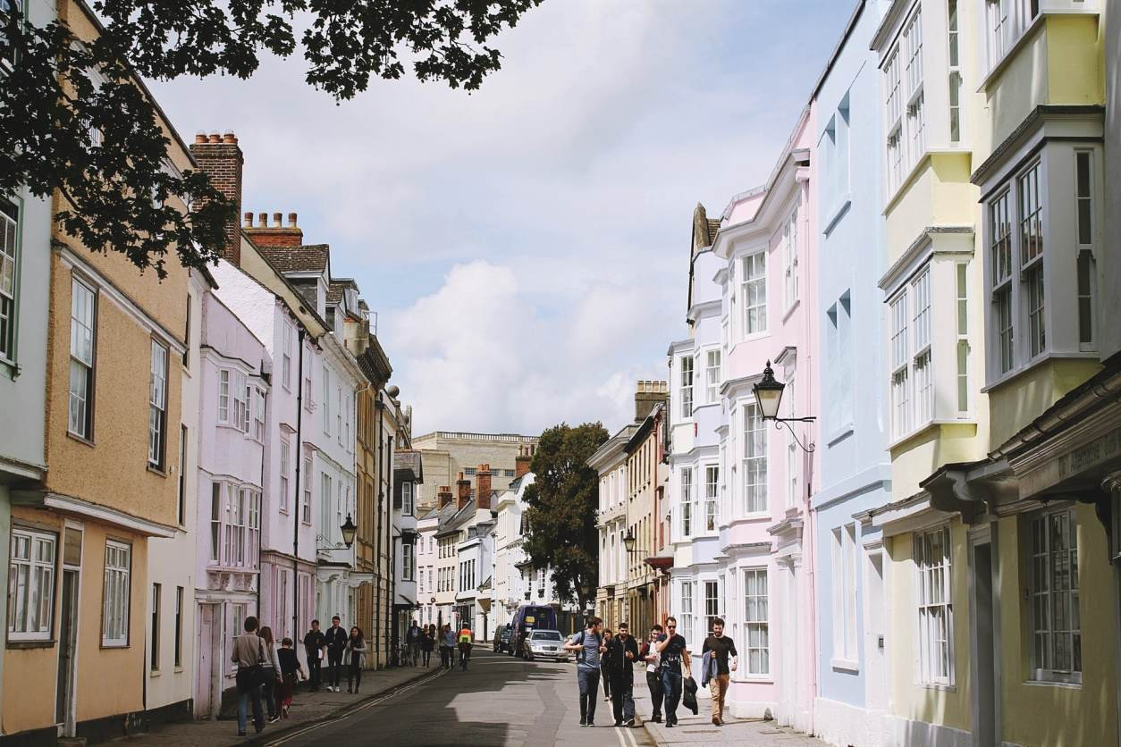 people-walking-down-british-city-street-with-colourful-pastel-buildings-in-oxford