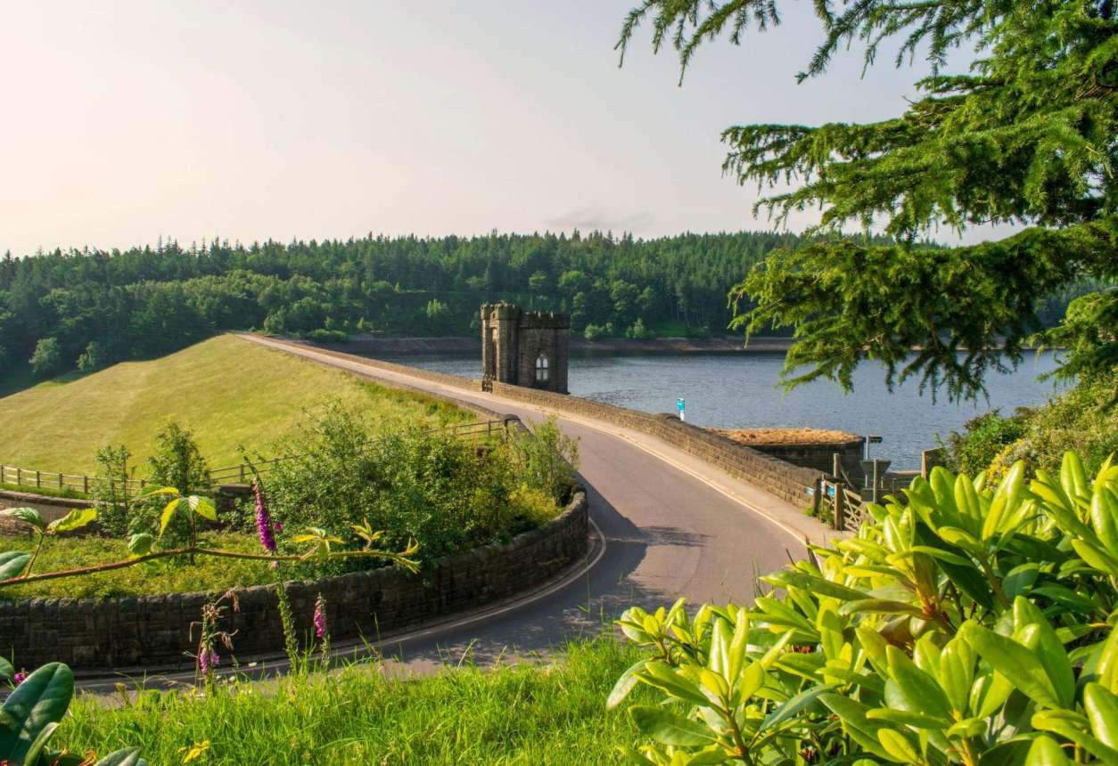 road-going-across-langsett-reservoir-with-a-grassy-field-on-the-other-side