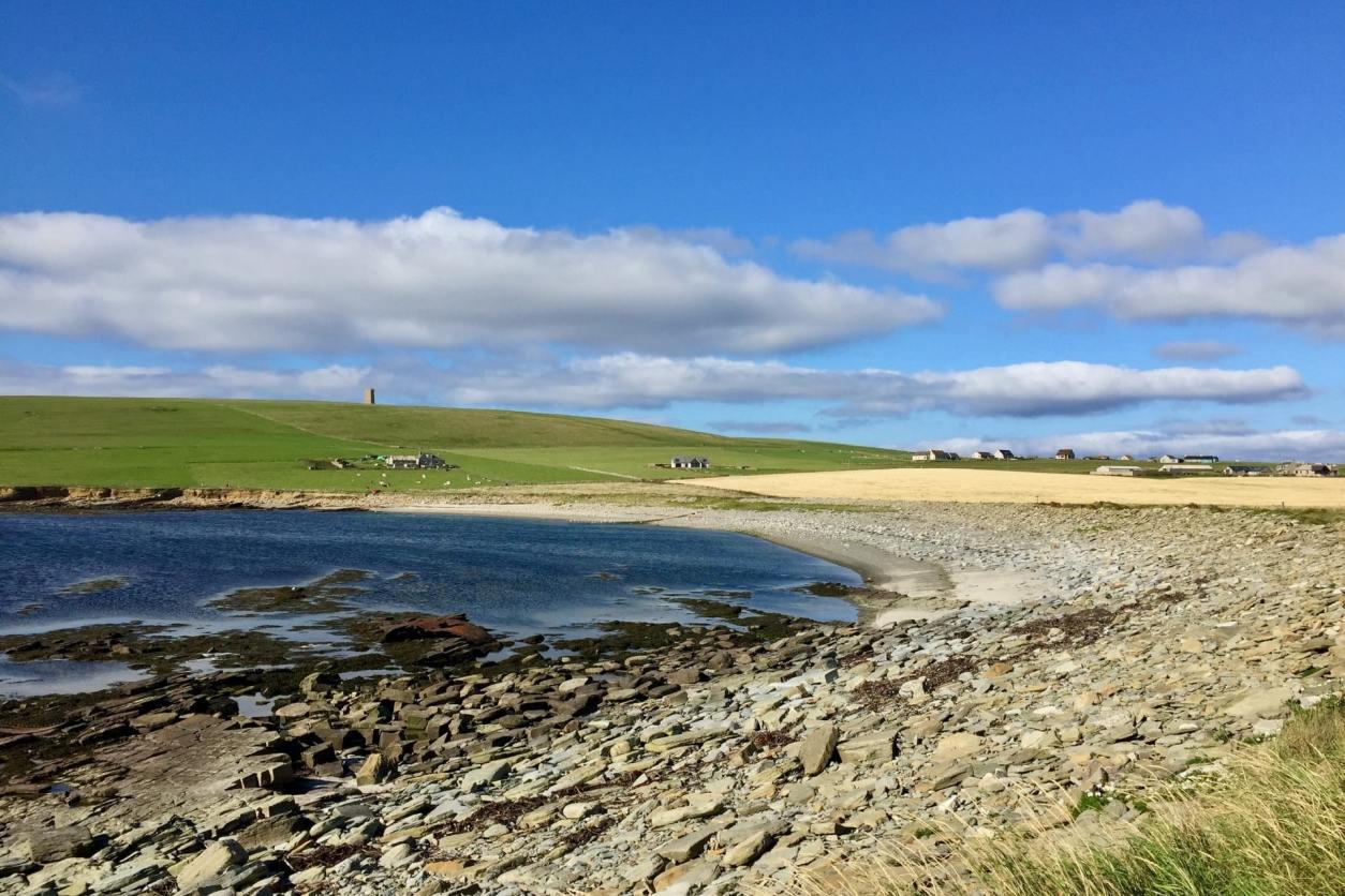 stone-beach-and-blue-ocean-with-green-fields-in-background-on-orkney-islands