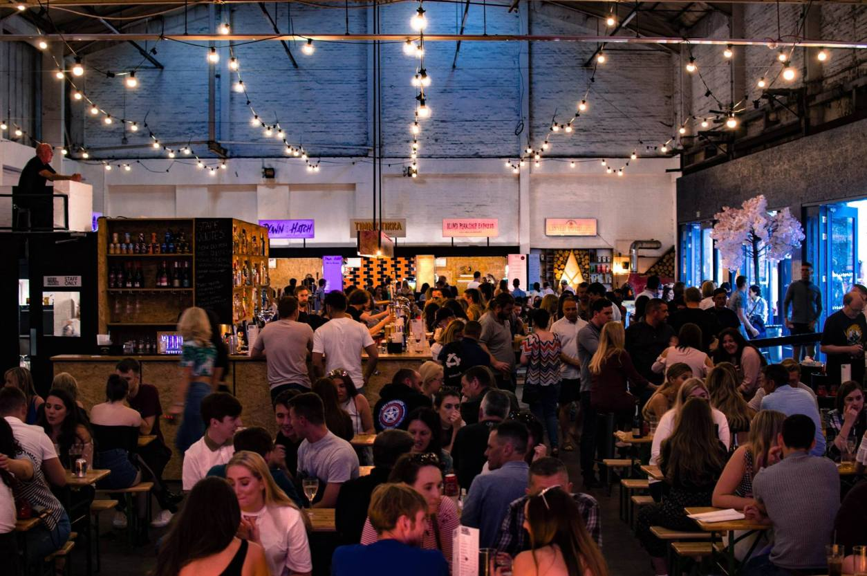 warehouse-packed-full-of-people-eating-and-drinking-at-indoors-street-food-market-baltic-market-weekend-in-liverpool-itinerary