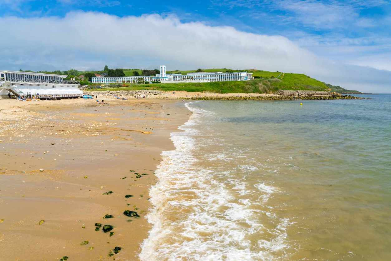 beach-with-buildings-and-hill-in-background-bowleaze-cove