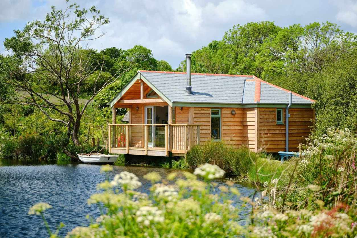 boat-house-log-cabin-with-boat-on-lake-surrounded-by-trees-best-airbnbs-in-cornwall