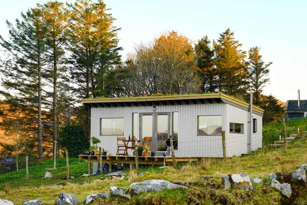 cosy-cabin-with-decking-in-front-of-trees-at-sunset-in-autumn