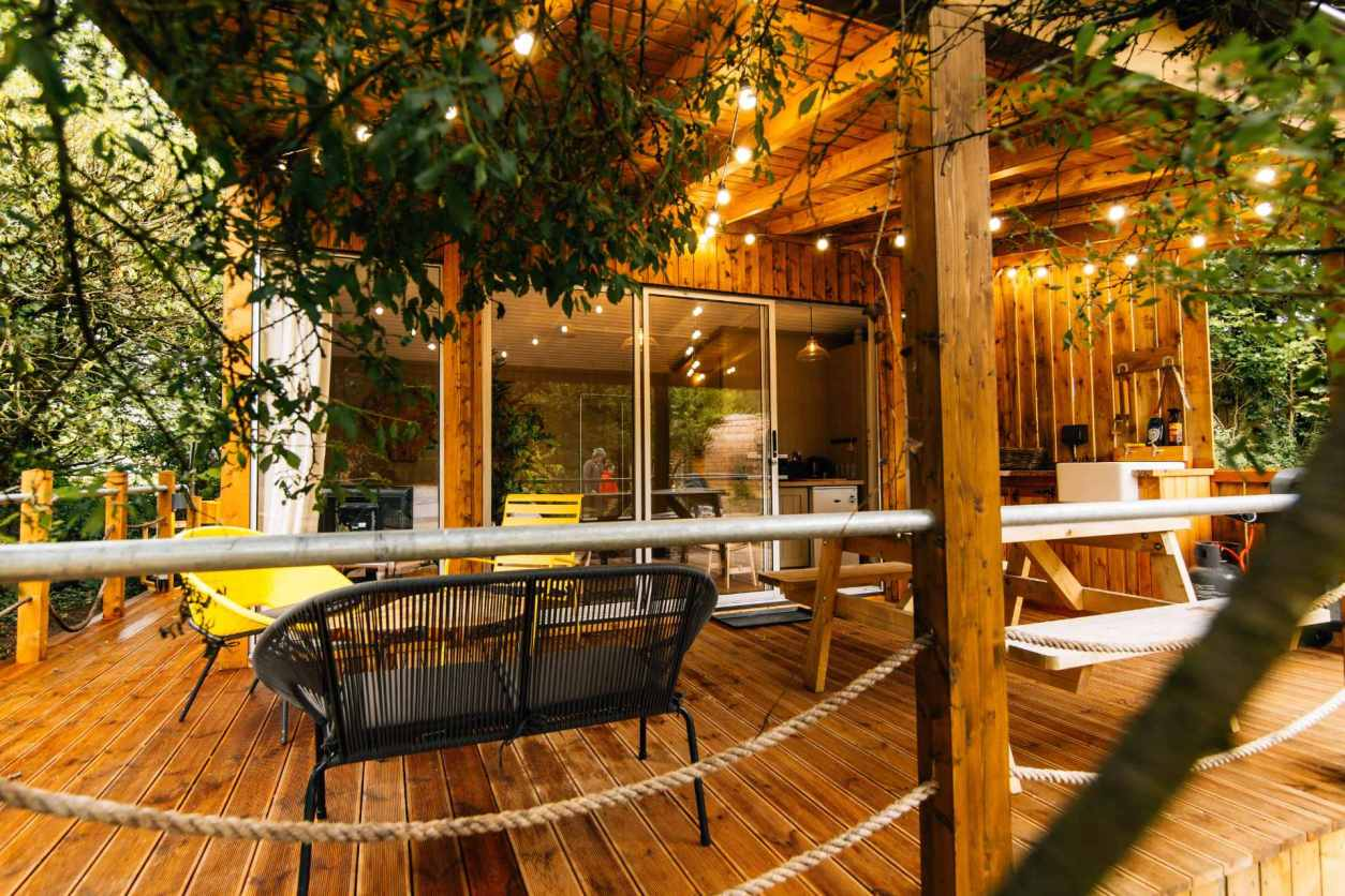 decking-with-seating-area-outside-wooden-lets-go-hydro-viking-hut-with-fairy-lights-glamping-northern-ireland