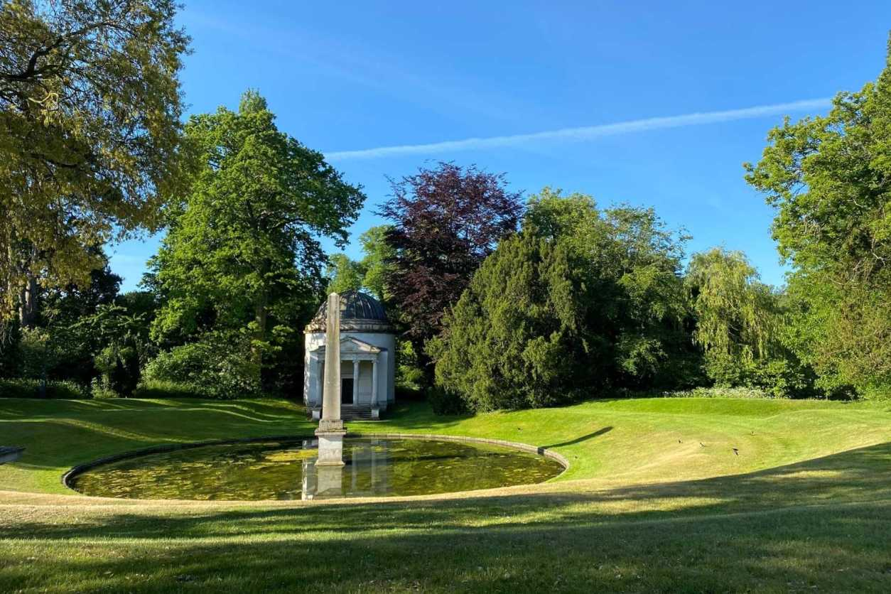 garden-surrounded-by-trees-with-pond-in-middle-against-blue-skies-chiswick-house-and-gardens