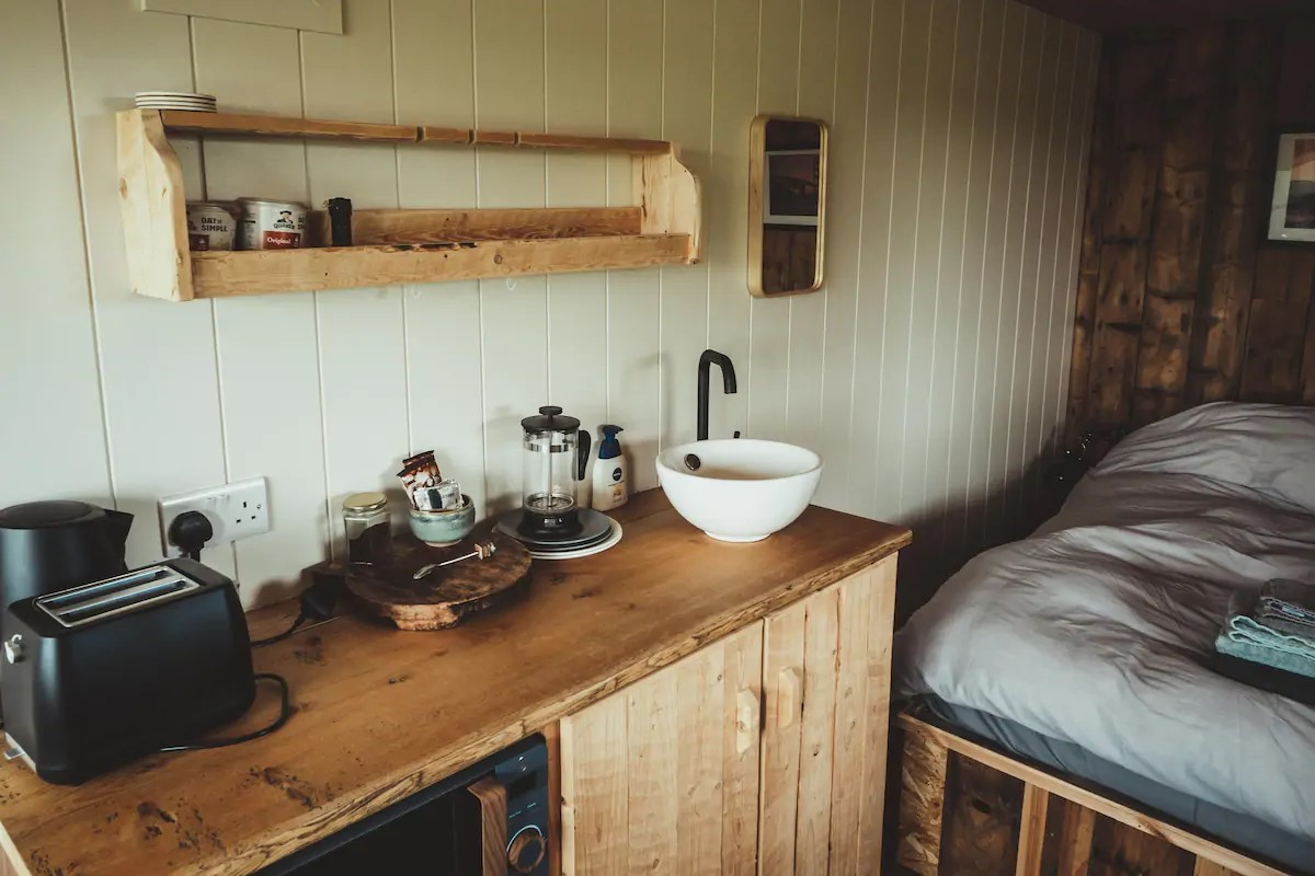 inside-rustic-cabin-kitchen-and-bedroom-at-the-surf-shack-causeway-coast-ballycastle