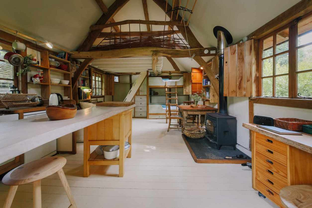 living-area-of-rustic-riverside-cabin-with-woodburner-in-constantine