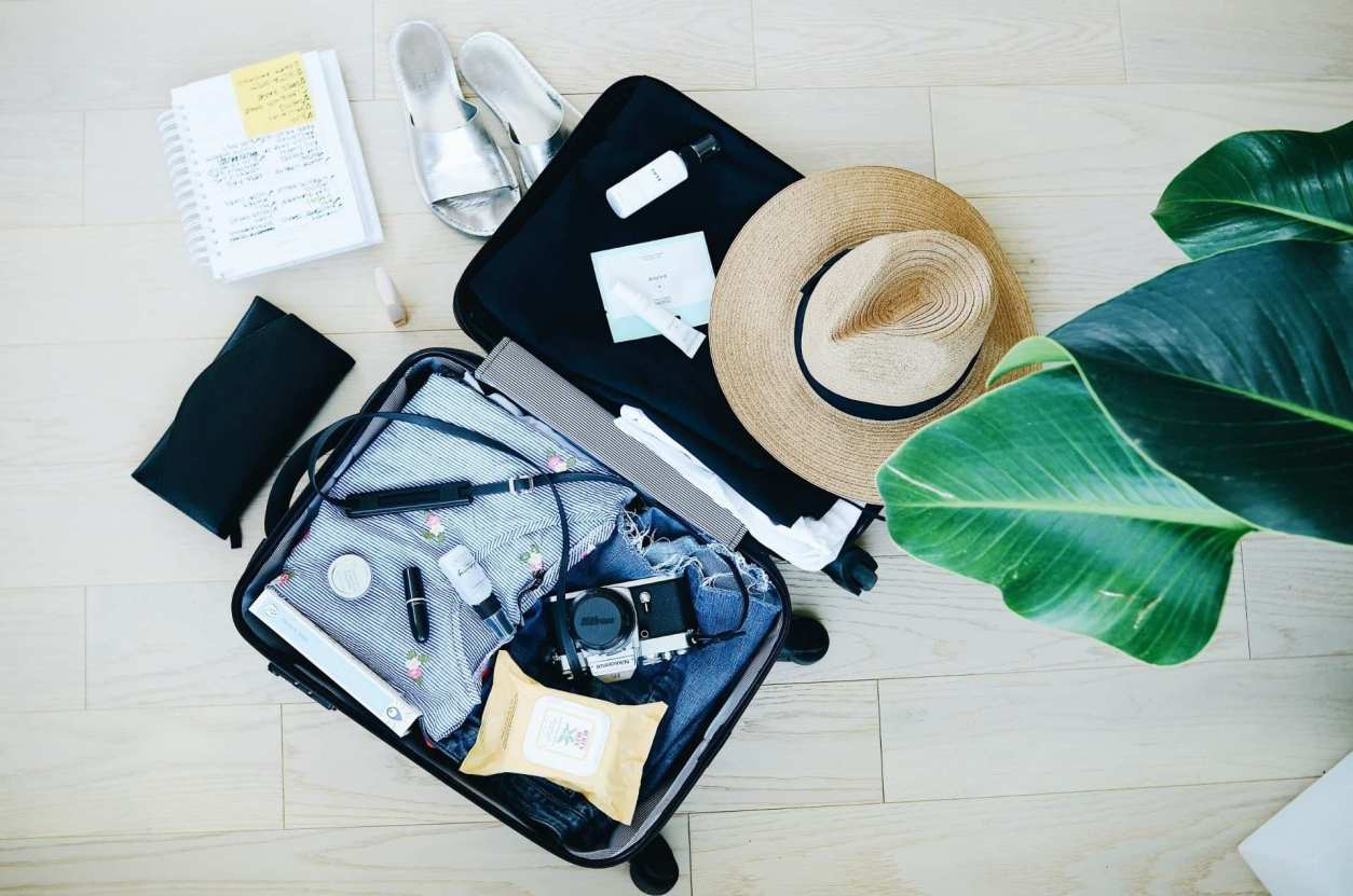 open-suitcase-lying-on-floor-with-clothes-hat-and-camera-in-it-travel-capsule-wardrobe