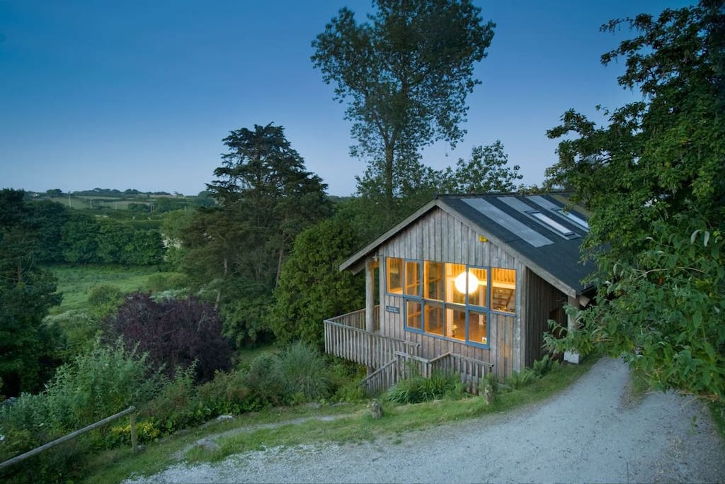 peaceful-country-treehouse-lit-up-at-sunset-in-field-in-penzance-best-airbnbs-in-cornwall