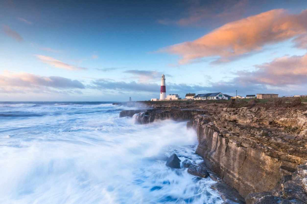 portland-lighthouse-on-rocks-by-sea-at-sunset-days-out-in-dorset