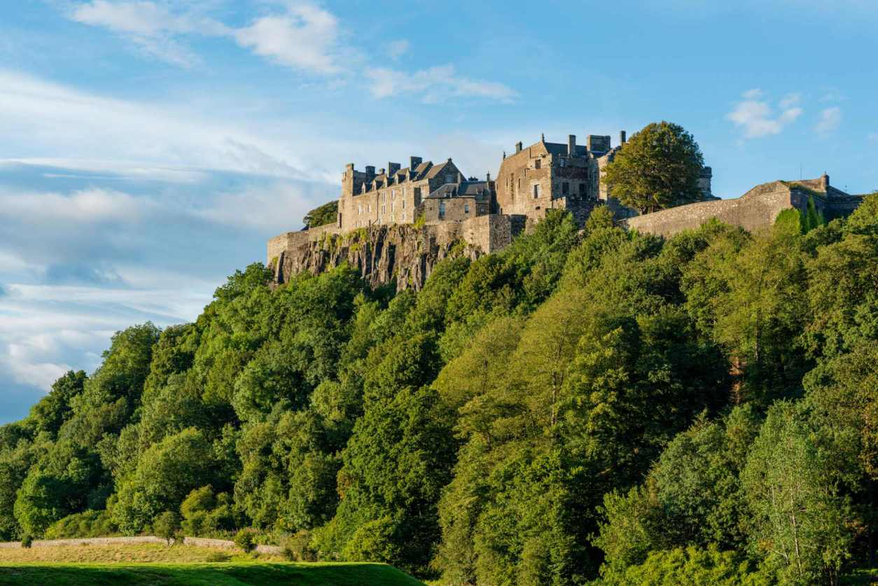 stirling-castle-on-hilltop-above-trees-on-sunny-day-day-trips-from-glasgow