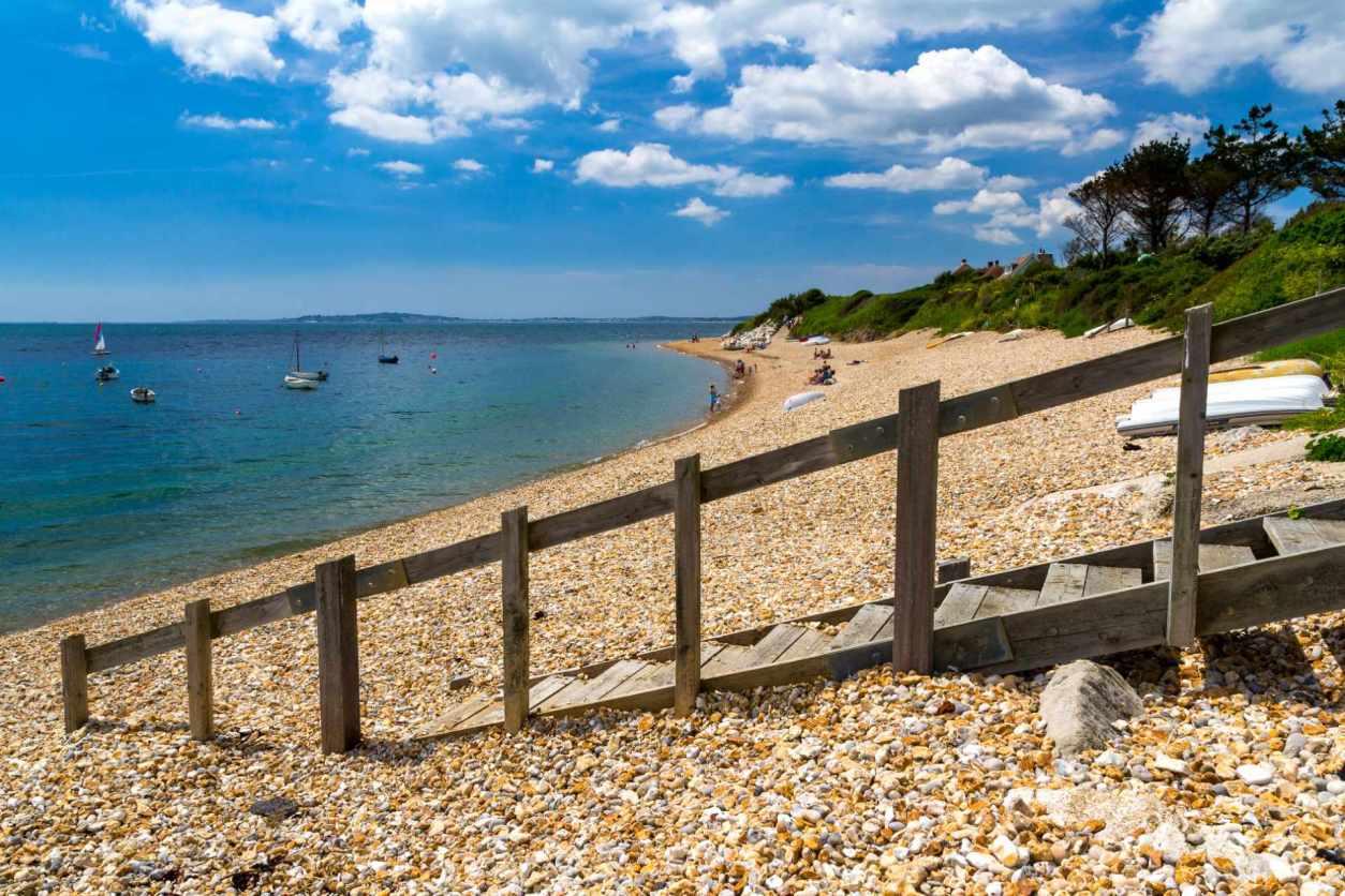 stony-beach-backed-by-trees-ringstead-bay