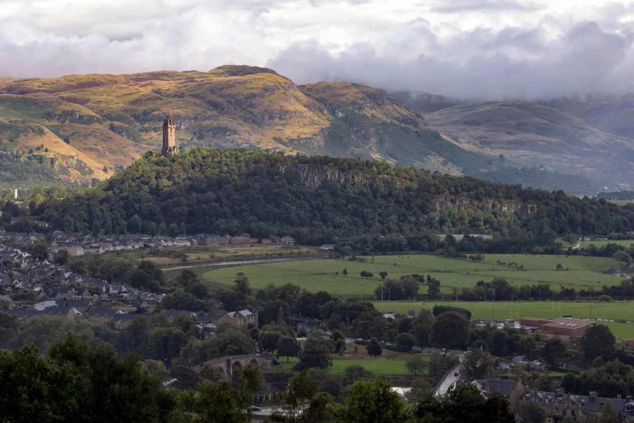 view-of-the-national-wallace-monument-and-surrounding-fields-and-mountains-in-stirling
