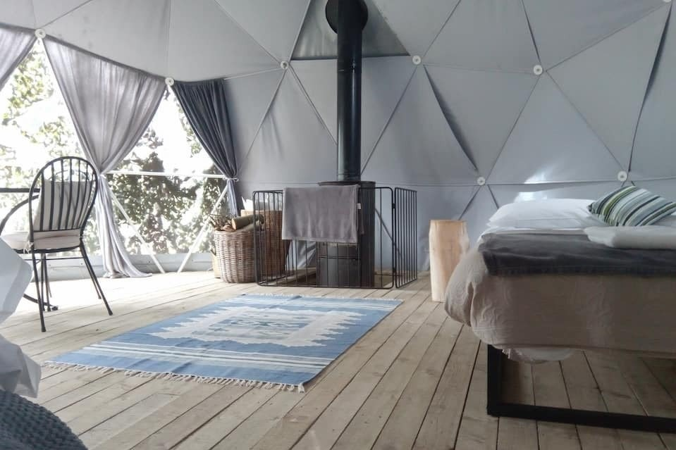 bed-woodburner-rug-and-chair-in-the-dome-glamping-in-grasmere