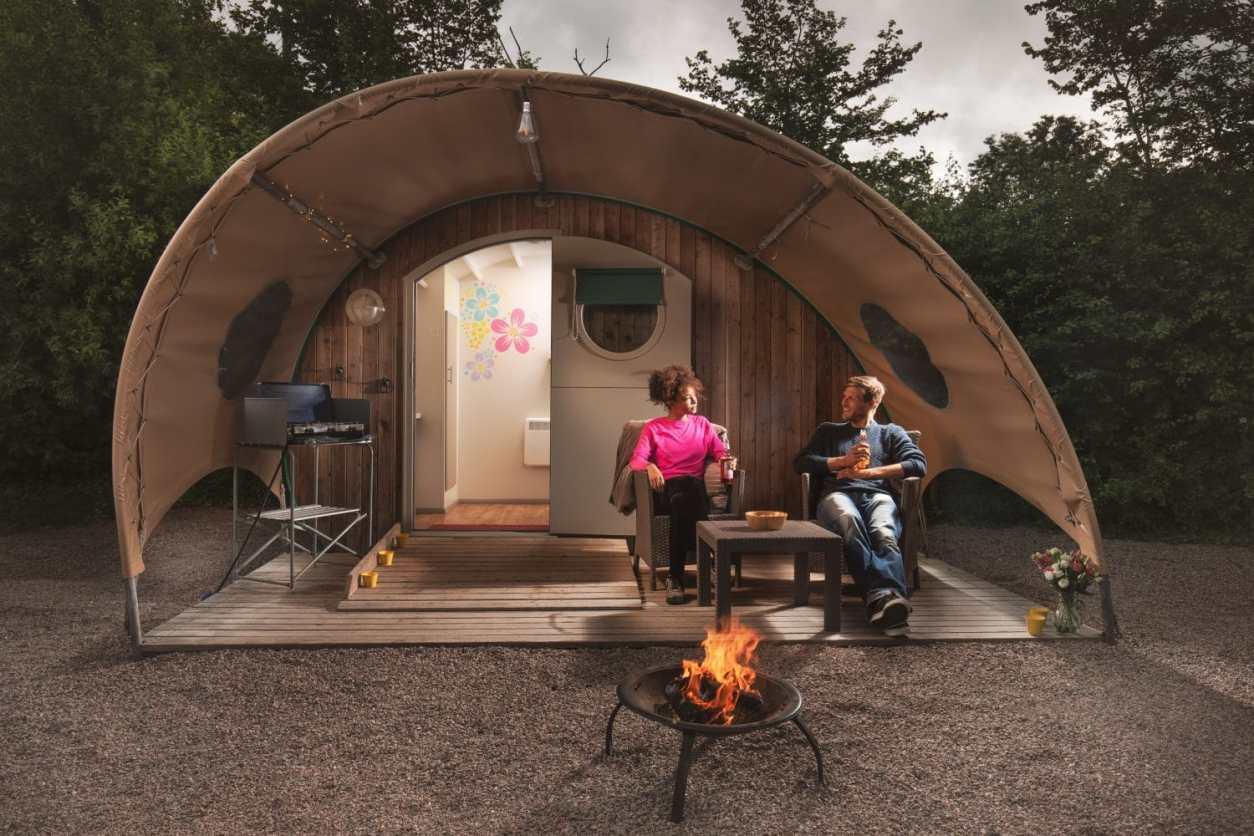 couple-sat-under-canopy-outside-old-oaks-pod-in-evening