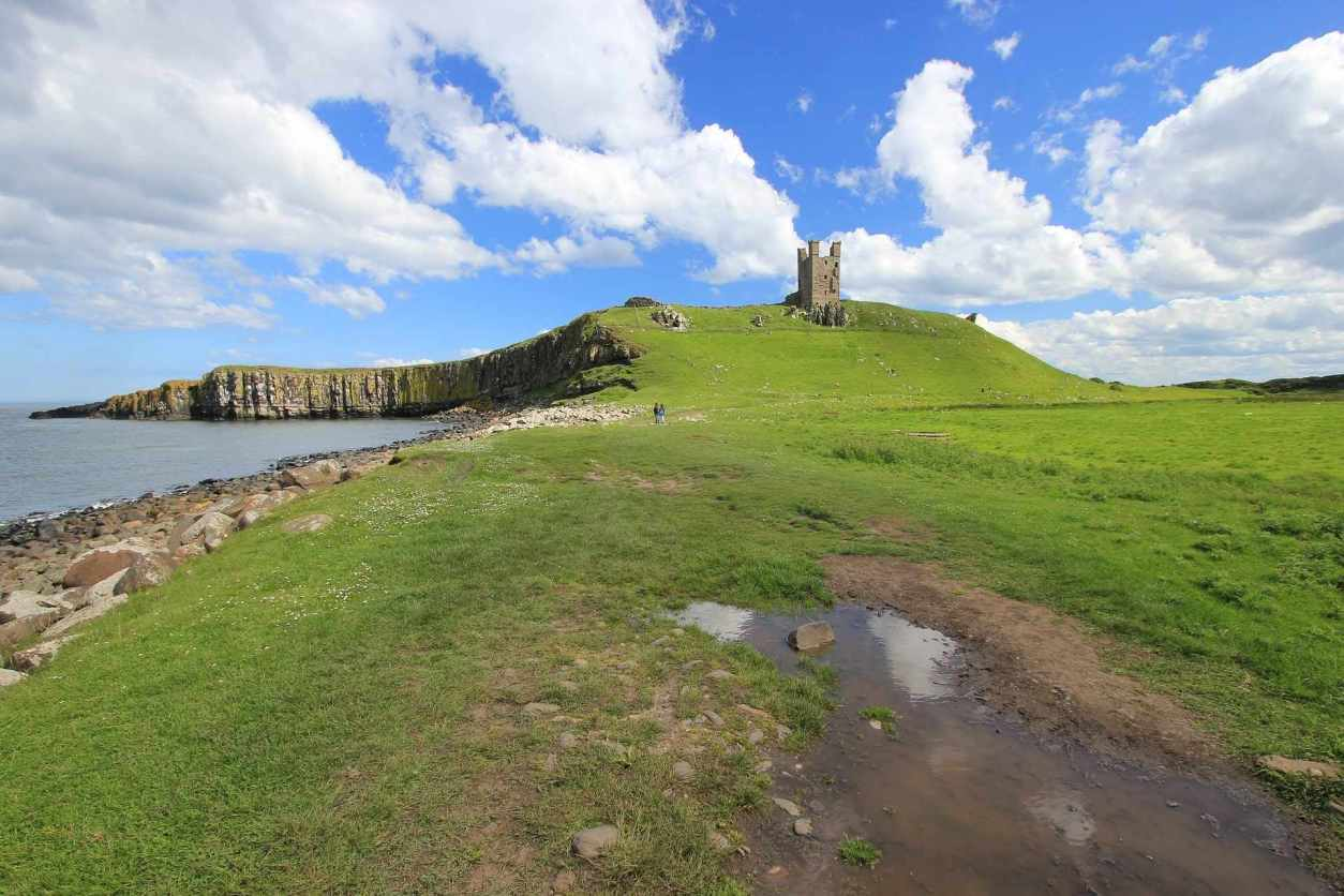 dunstanburgh-castle-up-green-hill-by-sea-on-sunny-day-in-embleton