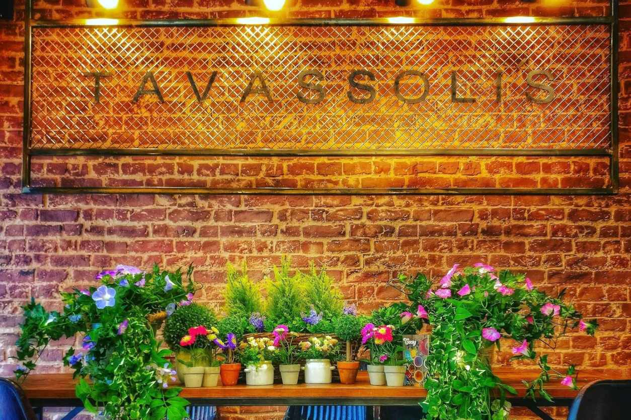 flowers-and-plants-on-table-in-front-of-brick-wall-with-tavassolis-sign