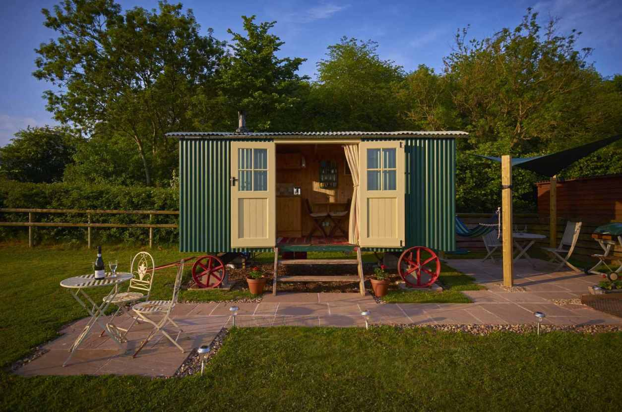 green-shepherds-hut-with-open-doors-in-field-at-upper-house-glamping