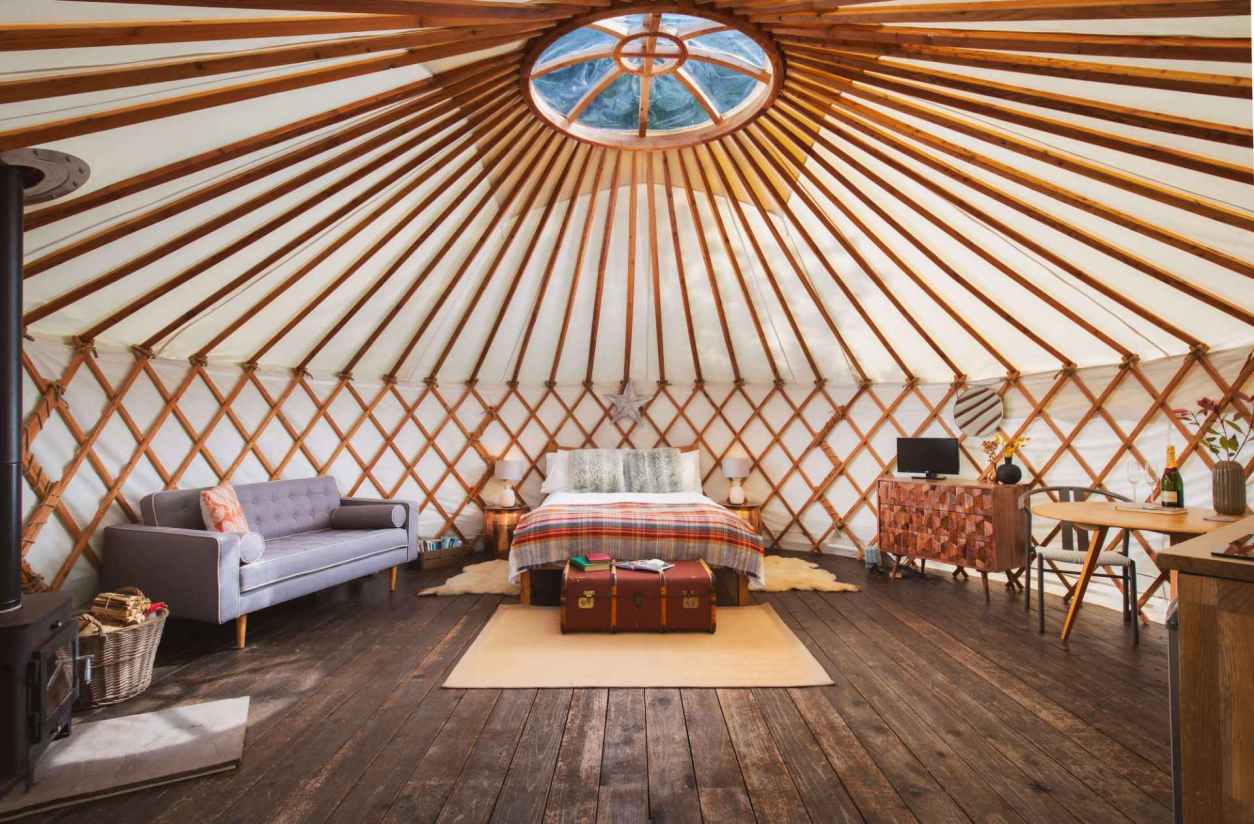 large-bedroom-and-living-area-inside-larch-yurt-at-the-yurt-retreat-glamping-somerset-somerset-glamping