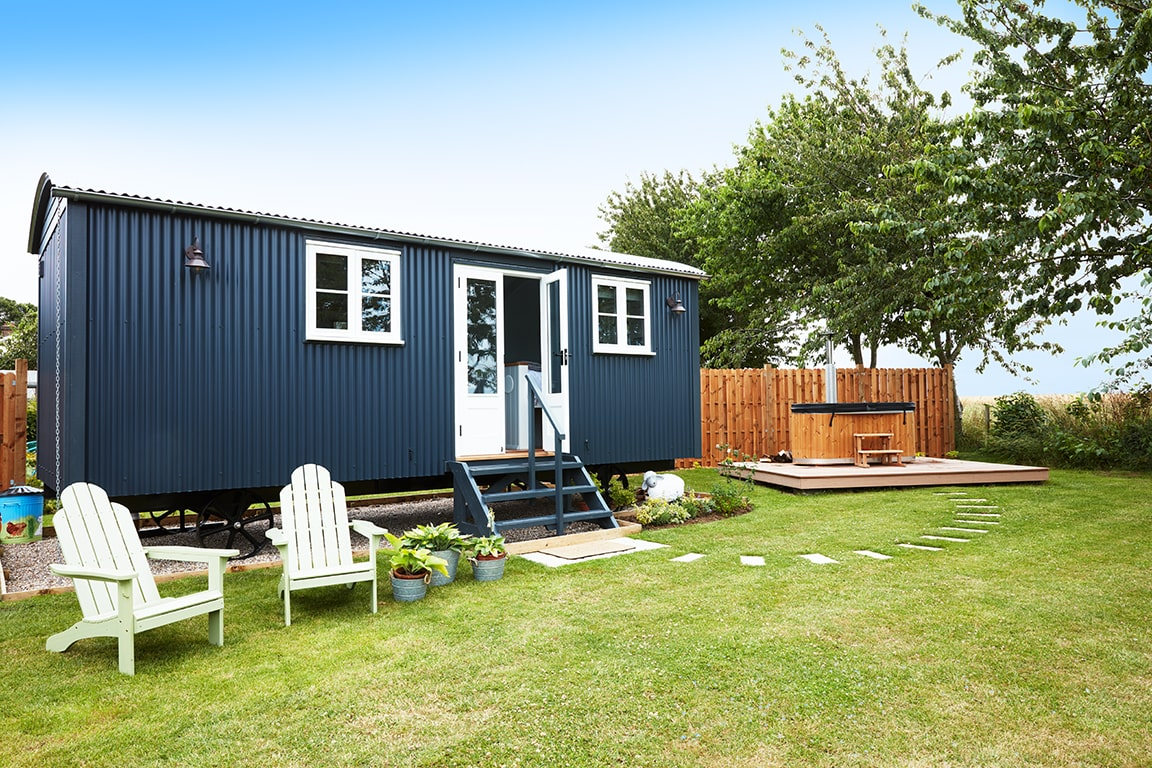 large-luxury-navy-shepherds-hut-in-field-with-woodfired-hot-tub-glamping-norfolk
