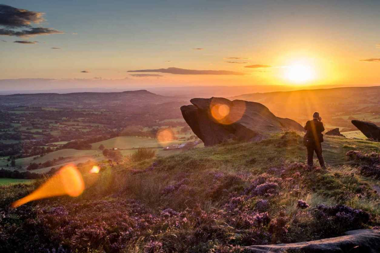 man-standing-on-top-of-hill-by-big-rock-at-sunset-the-roaches-and-luds-church