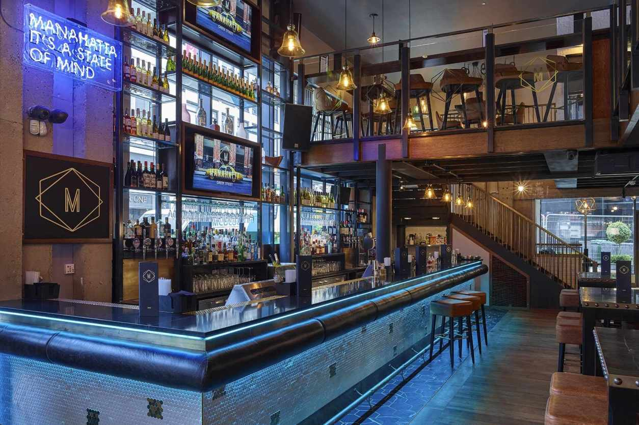 new-york-themed-bar-and-restaurant-lit-up-by-blue-lights-manahatta-leeds