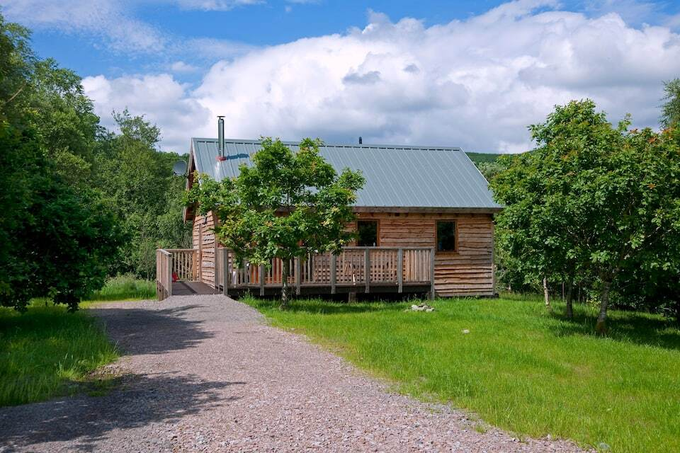 path-leading-to-oak-log-cabin-in-garden-on-sunny-day
