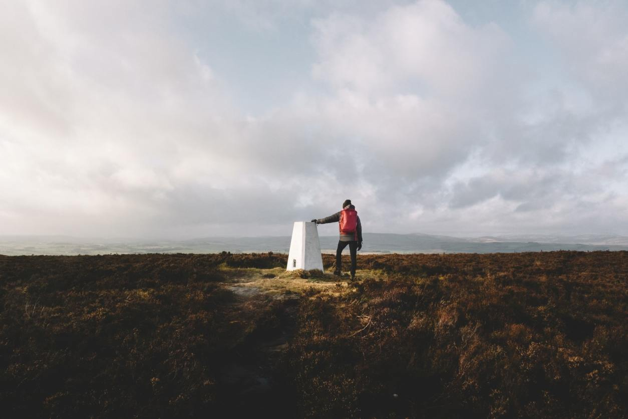 person-with-backpack-standing-by-trig-point-on-hill-at-sunset