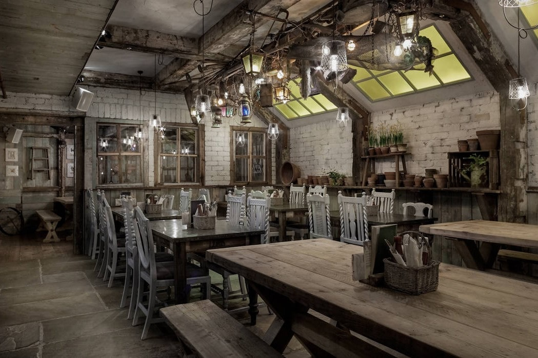 rustic-industrial-restaurant-room-with-tables-benches-and-chairs-at-the-botanist
