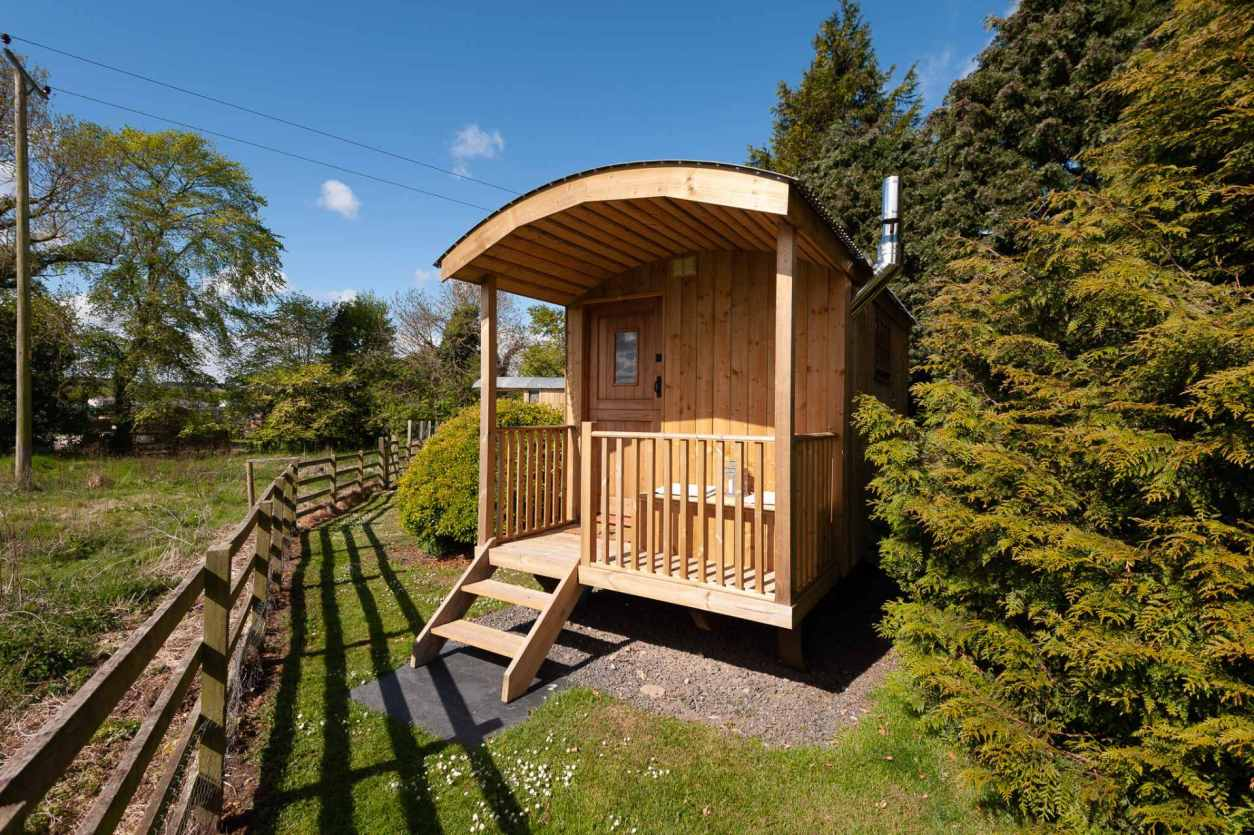 shepherds-hut-by-trees-at-lucker-mill-house-on-sunny-day