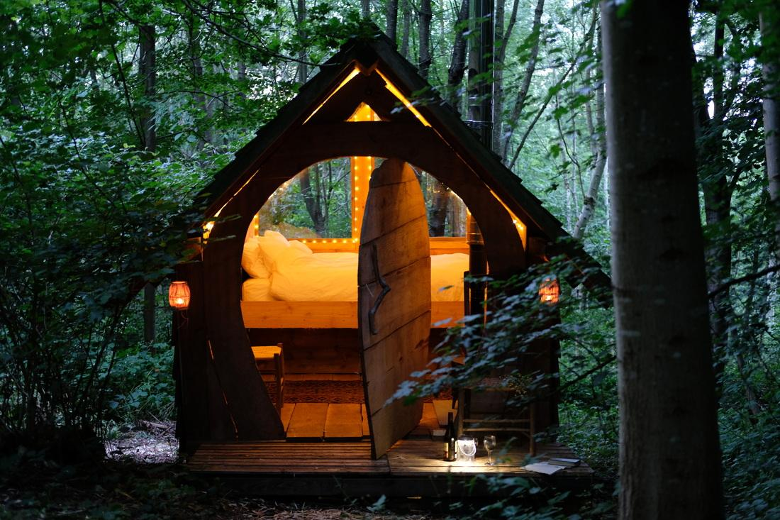 small-hobbit-house-lit-up-with-fairy-lights-in-evening-at-brook-house-woods-glamping-herefordshire