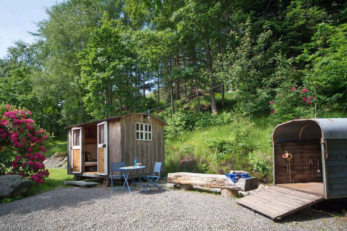 small-wooden-shepherds-hut-with-blue-seating-area-with-trees-in-background