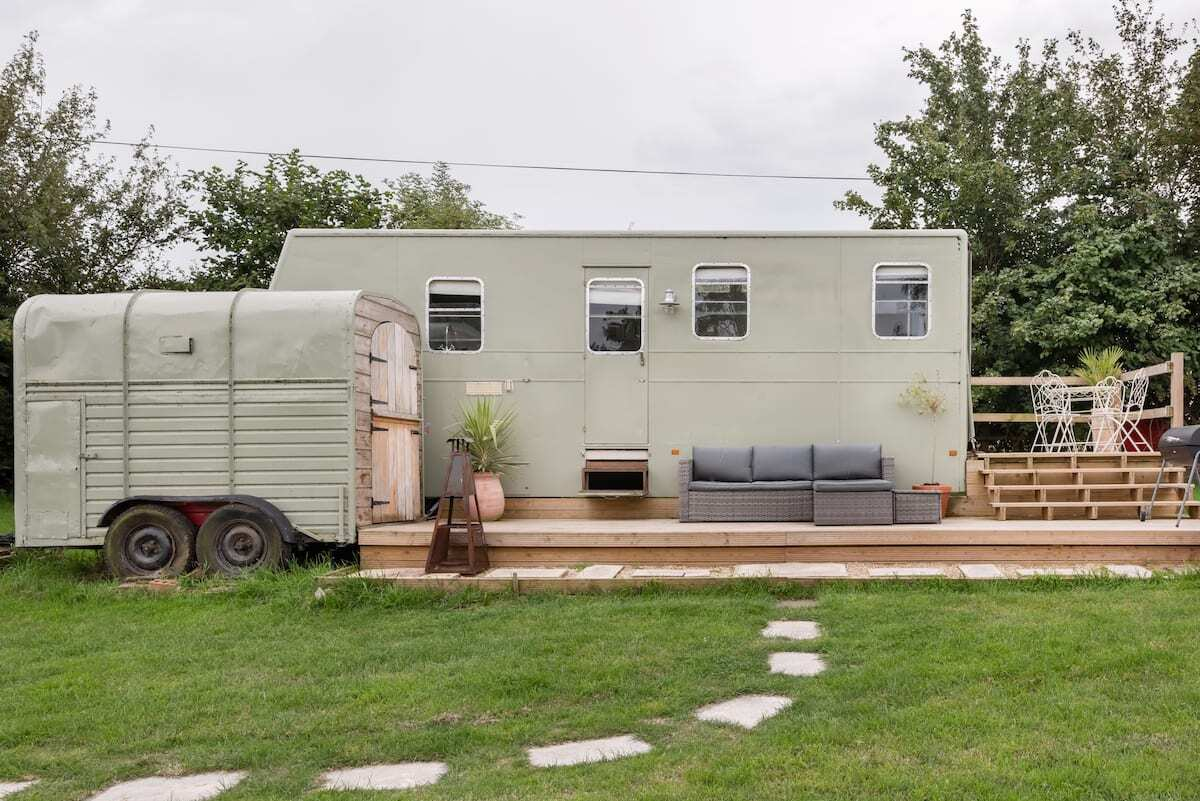 stepping-stones-leading-to-mint-vintage-horsebox-on-decking-in-garden