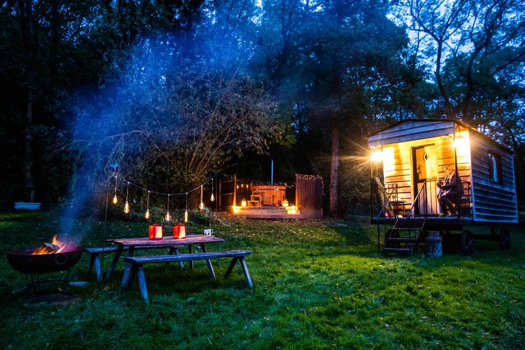 tawny-owl-shepherds-hut-hot-tub-picnic-table-and-bbq-lit-up-at-night