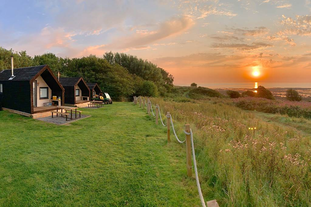 three-alnmouth-huts-in-field-by-beach-at-sunset