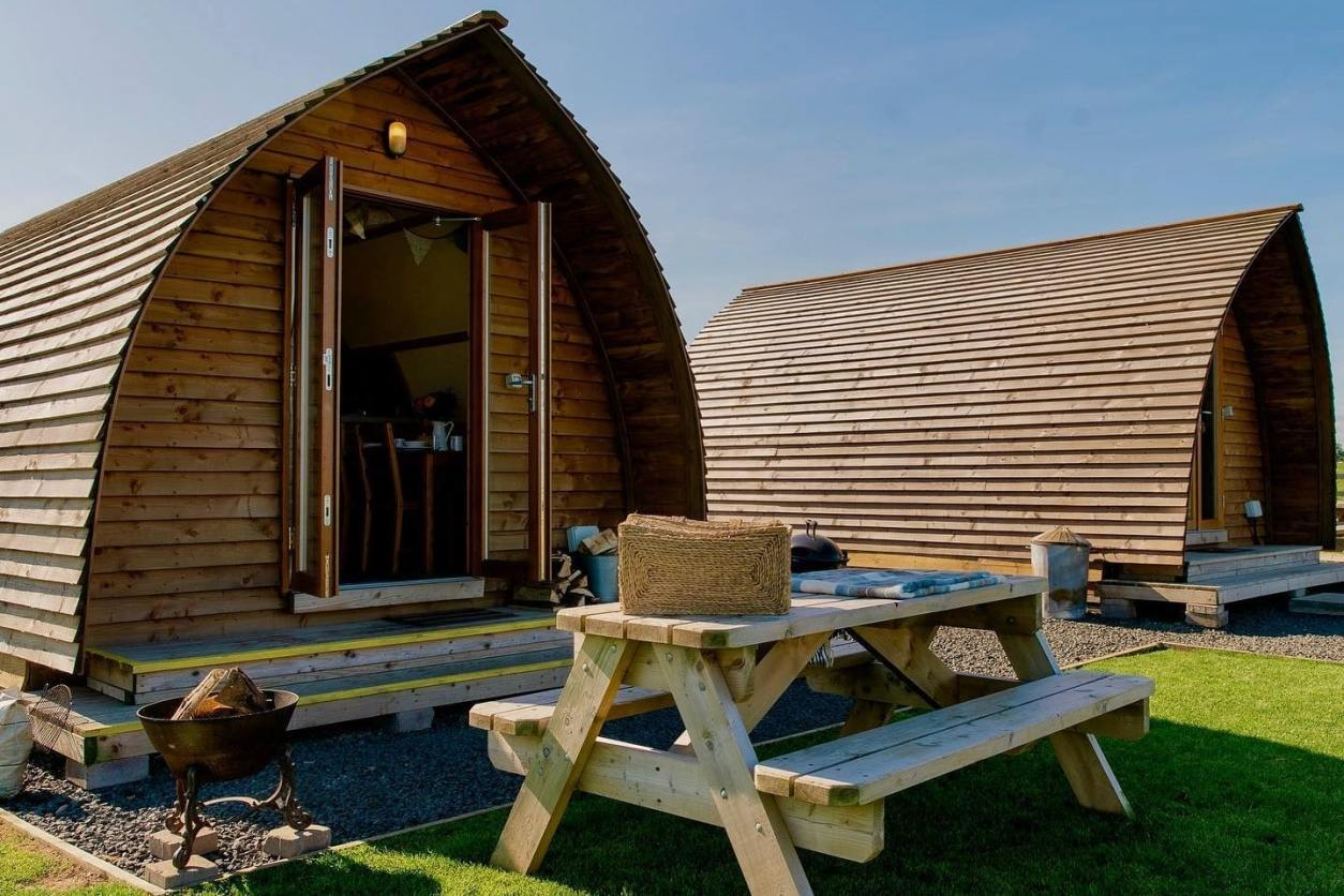 two-glamping-pods-in-field-with-a-picnic-table-at-springhill-farm-wigwams
