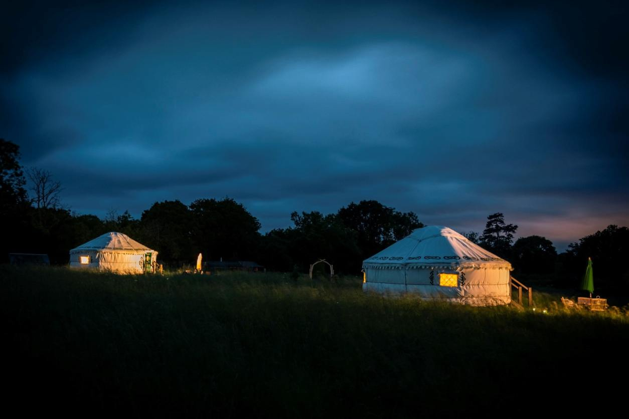 two-white-yurts-lit-up-at-night-at-the-wildflower-meadow