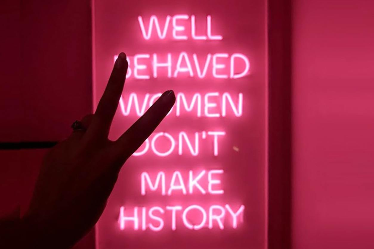 women-throwing-a-piece-sign-in-front-of-neon-pink-well-behaved-women-sign-at-tonight-josephine