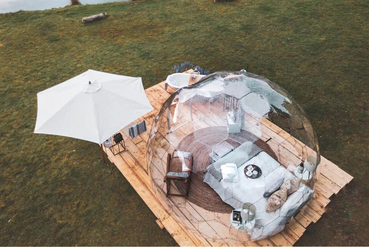 aerial-view-of-transparent-geodome-with-bed-in-field